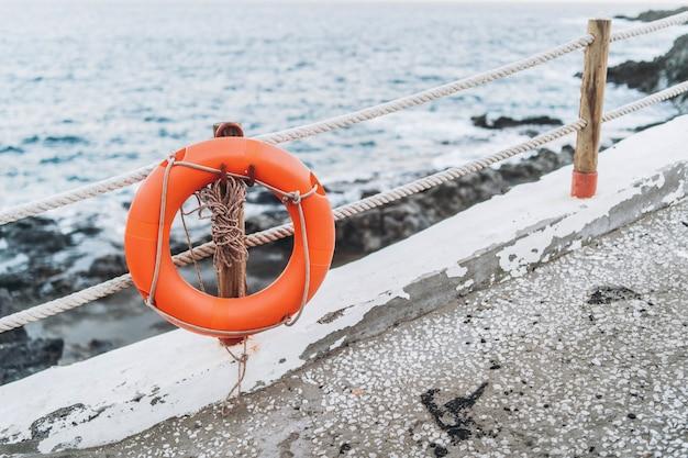 Красный аварийный спасательный круг висит на заборе возле пляжа.