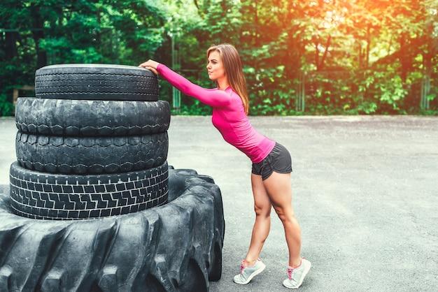 屋外の巨大なタイヤの近くのスポーティなかわいい女の子