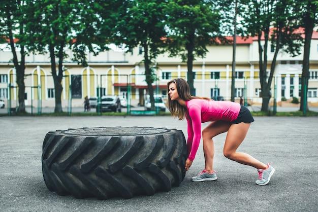 屋外巨大なタイヤを持ち上げるかわいいスポーティな女の子
