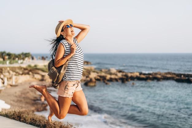 かわいい観光パンアジアの女の子が海の近くに屋外ジャンプします。