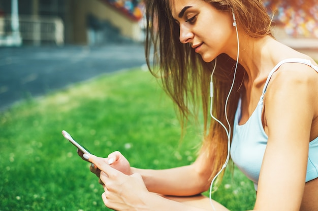 トレーニング後屋外でリラックスできる電話でスポーティなかわいい女の子