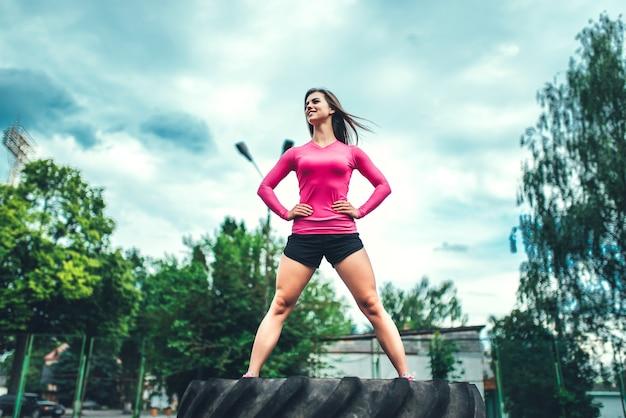 大きなタイヤと屋外かなりスポーティな女の子のトレーニング