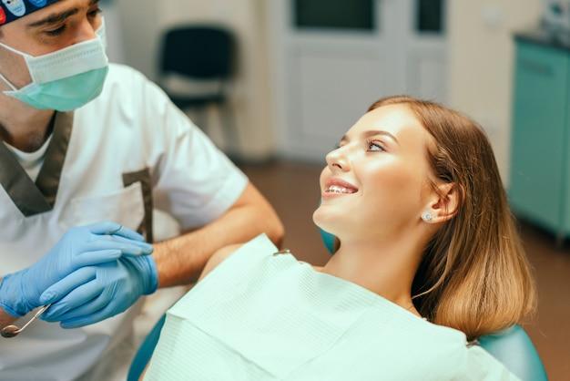 歯科医は歯科医院で中かっこで女性患者を診察します。
