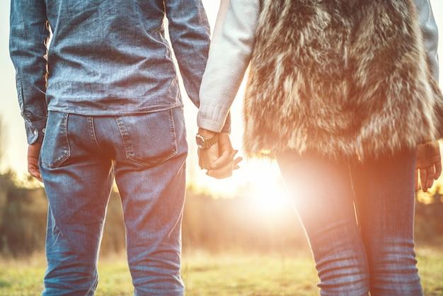 分野で手を繋いでいる愛のカップル。