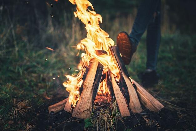 後ろでウォーミングアップの女の子と森の焚き火。