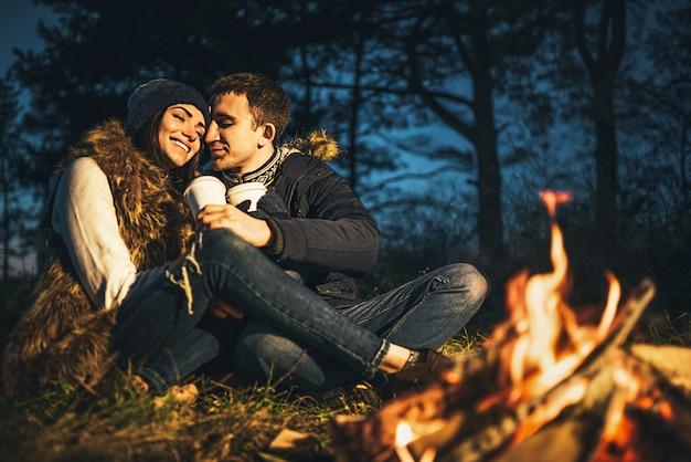 かなり若いカップルが焚き火の近くの森で熱い飲み物を飲みます。
