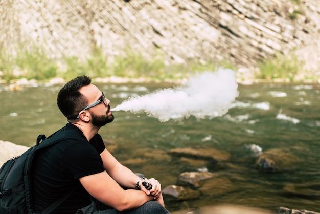 若い旅行者は山の川の近くの電子タバコを吸う