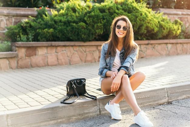 かなり若い笑顔ブルネットの少女路上屋外リラックス。