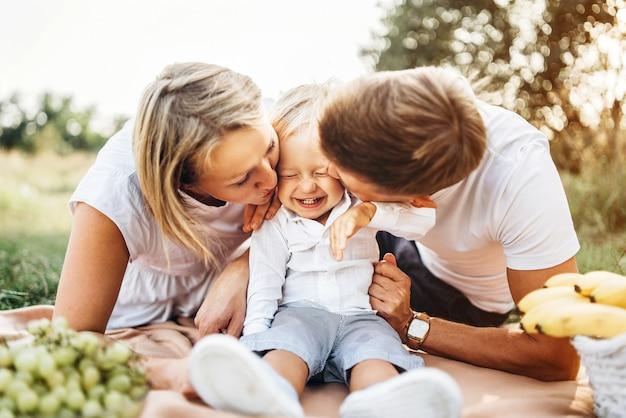 Молодые родители с маленьким мальчиком на пикник на открытом воздухе