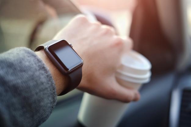 彼の手に時計が付いている車を運転する男