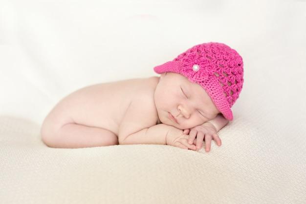 ピンクの帽子でかわいい眠っている新生児の女の子クローズアップ