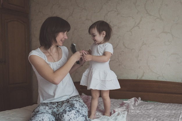 幼児の娘、暗い髪の若い母親のライフスタイル、パステルカラーをとかし、