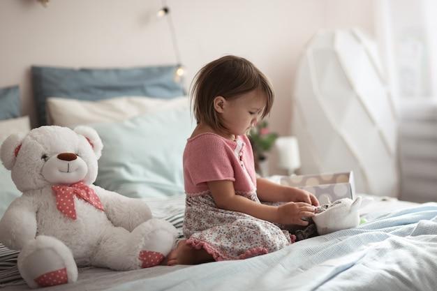 スカンジナビアスタイルの本当の寝室でベッドの上で子供します。