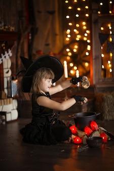 Маленькая ведьма хеллоуин читает заклинание над горшком детство хэллоуин,