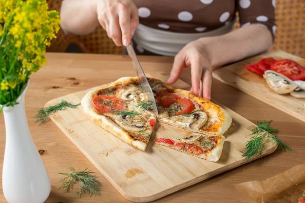女性の手が自家製の長方形のピザマルゲリータをキノコで切る。