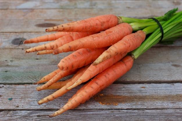 Молодая свежая морковь и зеленые травы на старых деревянных фоне. органическая еда