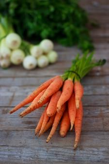 Молодая свежая морковь и зелень на фоне старых деревянных