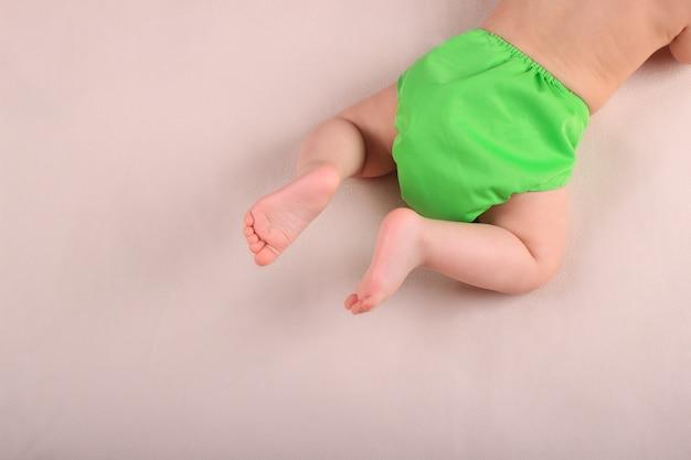 赤ちゃんの足と緑の再利用可能なおむつ。廃棄物ゼロのベビーケアのコンセプト。