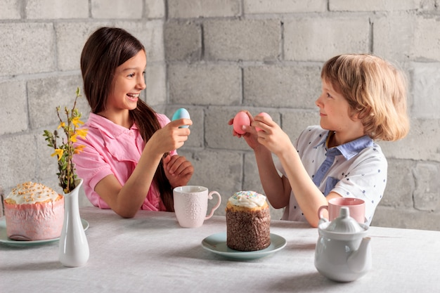 Счастливая маленькая девочка и мальчик, играющий в традиционную пасхальную игру - постукивание яйцами с крашеными яйцами дома