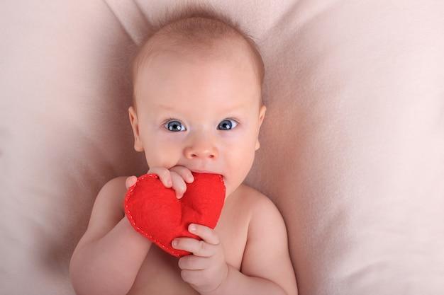 赤いおもちゃの心を持つかわいい赤ちゃん。愛と家族の概念