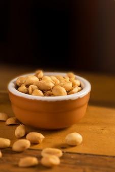 ローストと塩漬けのピーナッツは、木製のテーブルの上に折ります