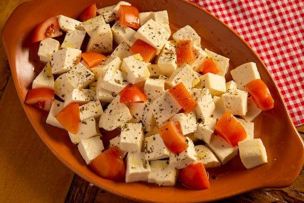 トマトをみじん切りにした半熟チーズと油とオレガノの味付け
