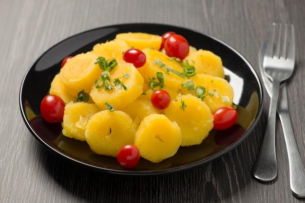 Приготовленная маниока с помидорами черри