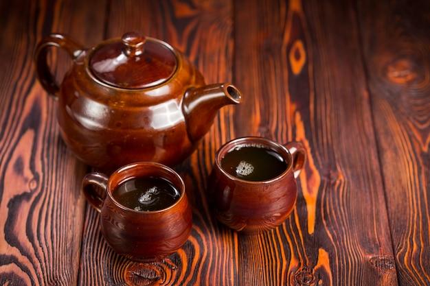 木の上の緑茶とカップ