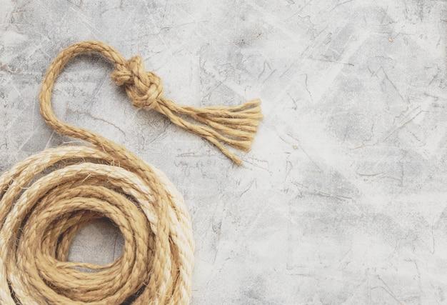 灰色の背景に結び目で結ばれたロープ