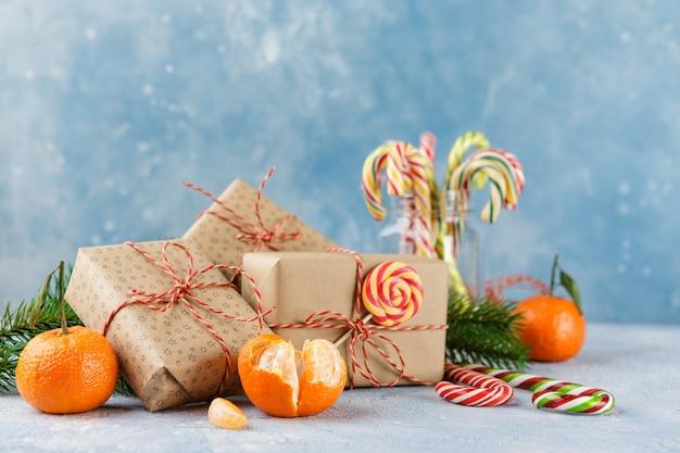 Рождественская подарочная коробка, конфета, мандарины и ветка ели