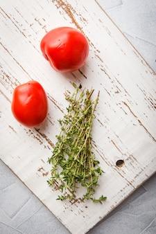 Ветви тимьяна и два помидора на светлом фоне