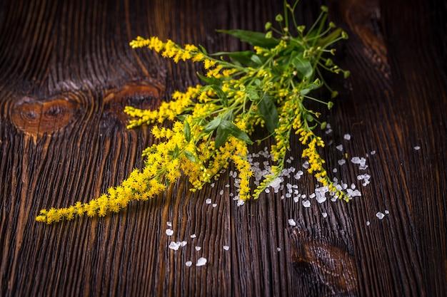 野生の花と木のテーブルに塩