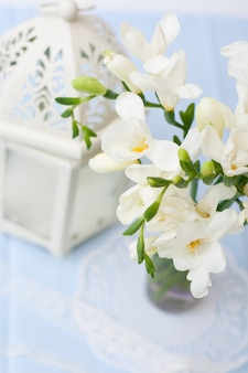 花と装飾的なボトルのつぼみと白いフリージアの枝