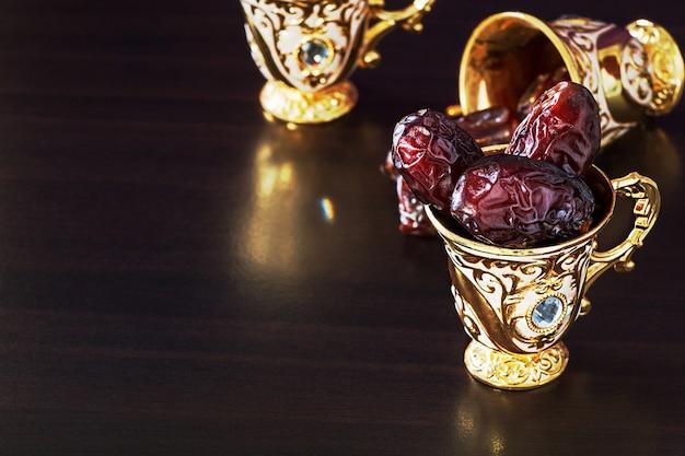 日付とミニカップで設定された金色の伝統的なアラビアコーヒーのある静物。
