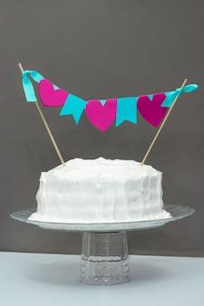 お祝いバナーと白のフロスティングバニラバースデーケーキ。灰色の背景お祝いの概念