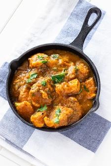 伝統的なインドのバターチキンカレーをクローズアップし、レモンとタオルの上に鉄キャストでチャパティパンを添えて。上面図。