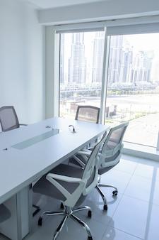 窓からの壮大な景色を望む会議室。オフィスの椅子と会議用テーブルビジネスや事務作業の概念。