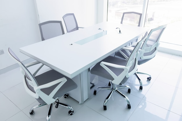 窓からの壮大な景色と空の新しい会議室。オフィスの椅子と会議用テーブルビジネスや事務作業の概念。
