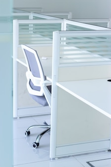 椅子とオフィスのテーブルを持つ空の新しいオフィス。ビジネスや事務作業の概念。