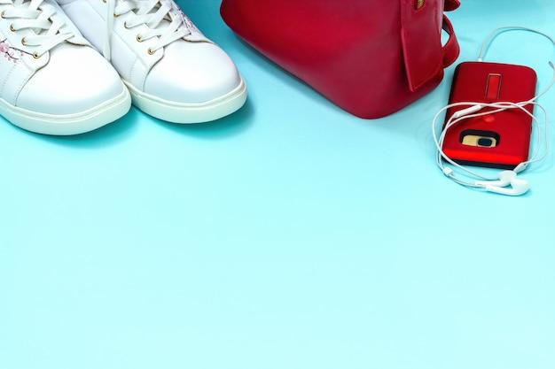 カジュアルスポーツ服は若い女性のために設定します。白と赤のアクセサリー青い背景。