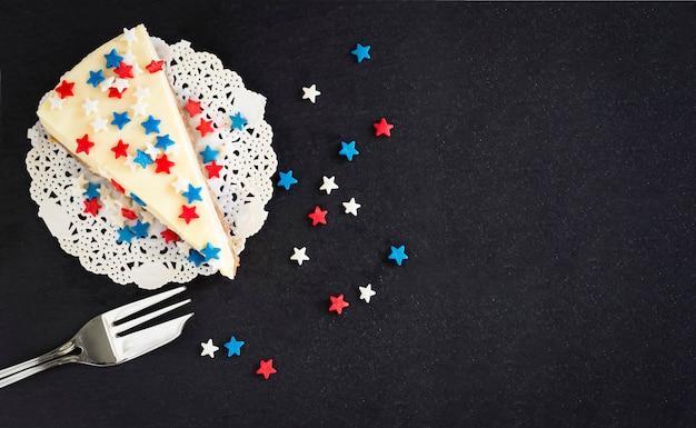 スレートボード上のプレーンニューヨークチーズケーキをスライスします。