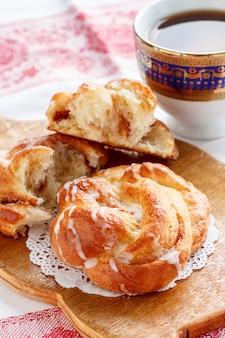 Свежая домашняя сладкая булочка с корицей с глазурью и черный кофе на завтрак.