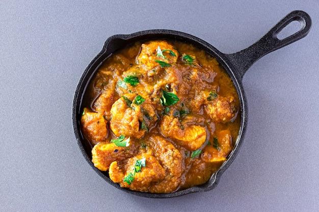 伝統的なインドのバターチキンカレーとレモンは、鉄キャストで提供されました。上面図。伝統的な世界の料理。