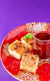 Чай и три кусочка манной каши или торта басбоуса или намура - традиционные арабские сладости с орехами, вода апельсинового цвета. копировать пространство сиреневый космос.