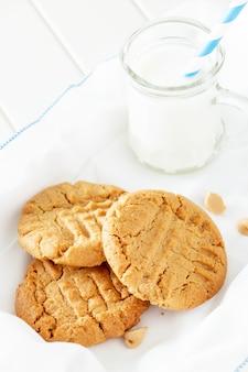 ミルクのマグカップとおいしい自家製ピーナッツバタークッキー。白い木の空間。健康的なスナックやおいしい朝食のコンセプト。