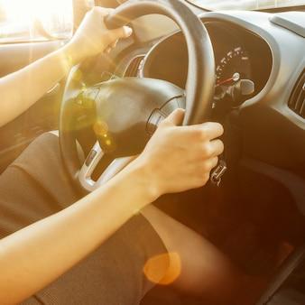 女性の手がクローズアップ、ステアリングホイールを握ります。女性が車を運転しています。