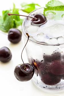 ガラスのチェリー、ミントおよびアイスキューブが付いている冷たいさわやかな解毒水。