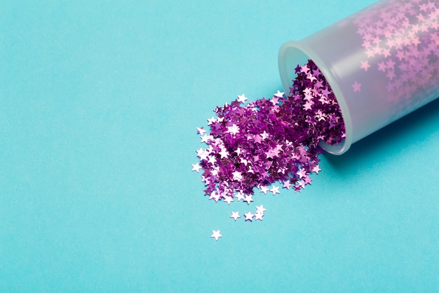 キラキラ背景。紫色のキラキラ星が色付きの背景に散在しています。休日のコンセプト