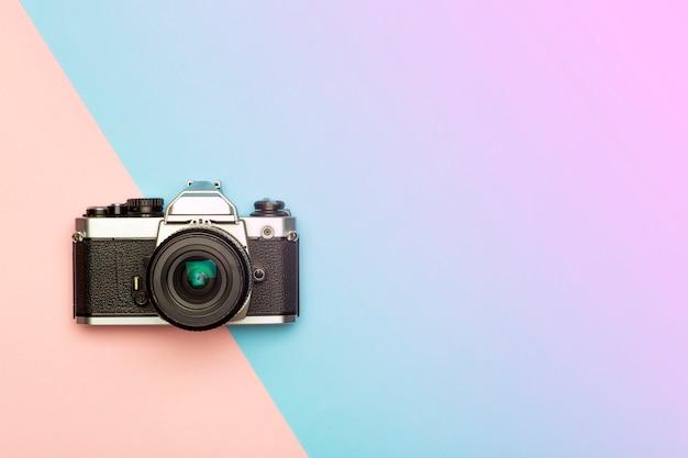 写真カメラの創造的なコンセプトの背景。色付きの背景にビンテージレトロな写真カメラ。旅行、休暇、写真のコンセプト