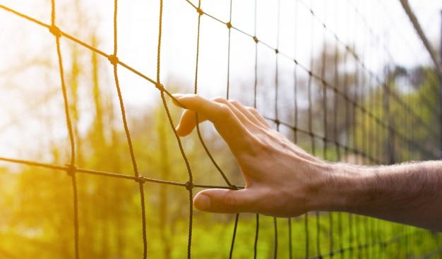スポーツコンセプト男は日没時のスポーツ分野でバレーボールのネットを持っています。